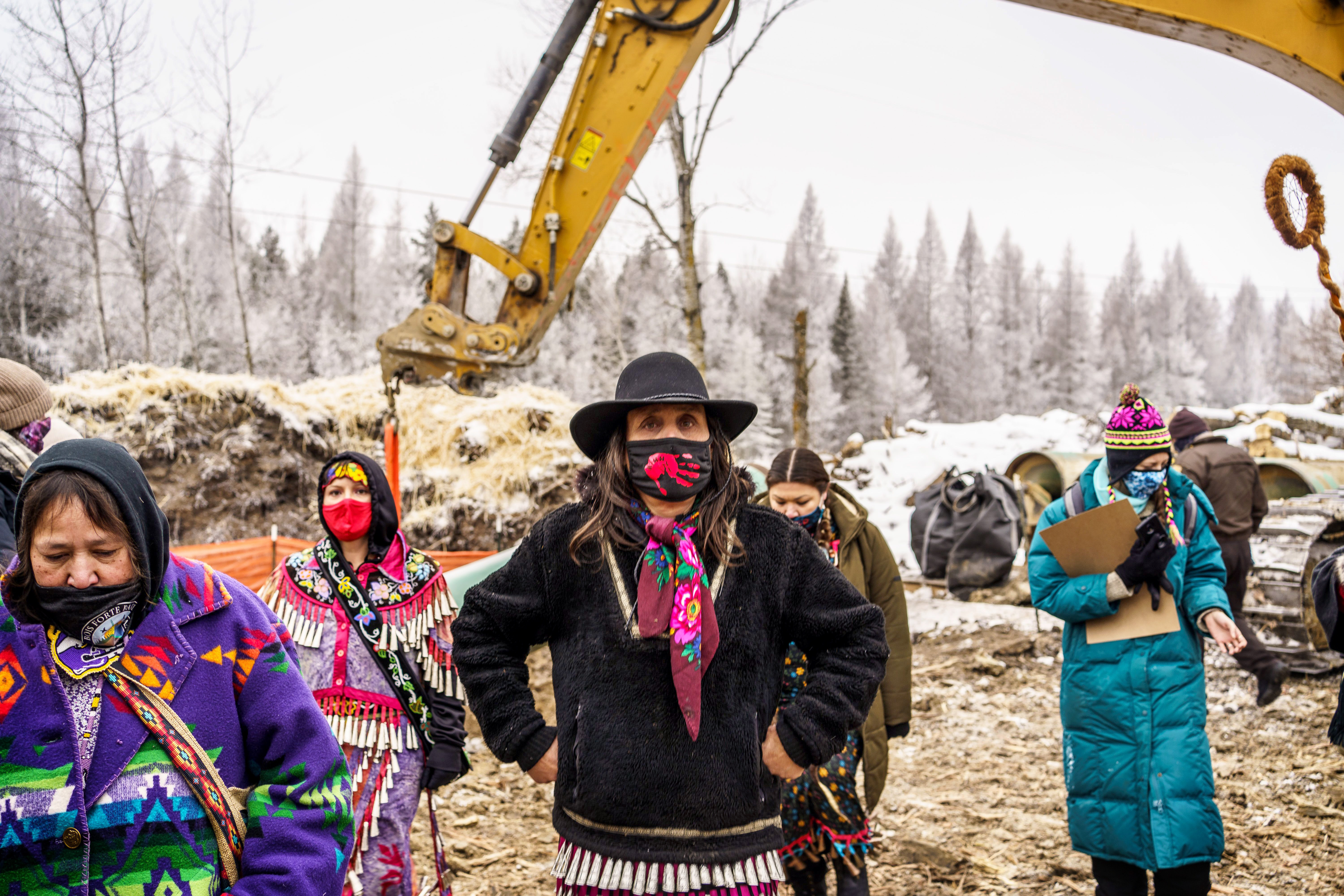 Winona LaDuke, center, and water protectors stand in front of the Line 3 construction site in January. Winona's hands at her hips. She has on a black mask, with a red handprint across the front of the mask. Large yellow crane in background. Water protectors dressed in indigenous garb and wearing masks.