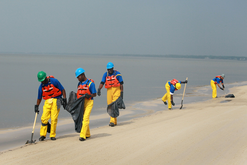 Workers clear a Mississippi beach of debris to prepare it for possible contamination after the Deepwater Horizon spill in 2010.