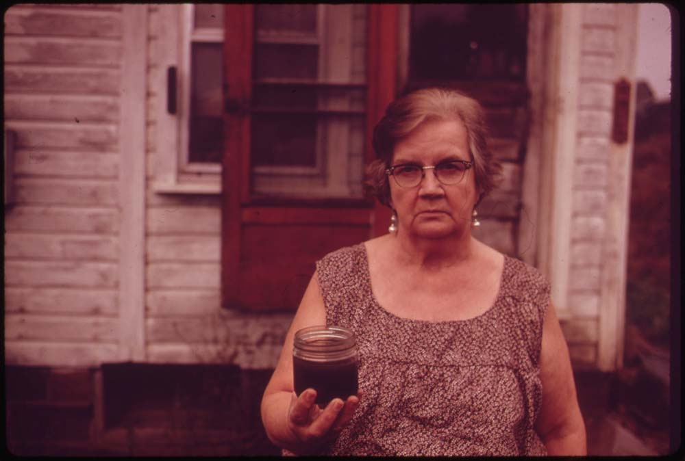 October, 1973: Mary Workman holds a jar of undrinkable water that came from her well near Steubenville, Ohio. She has to transport water from a well many miles away, and she has filed a damage suit against the Hanna Coal Company.