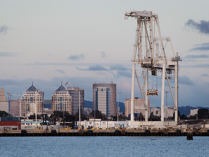 The Oakland skyline, behind the Port of Oakland. The Port is one of the largest container ship facilities on the West Coast and the site of the new bulk export terminal.