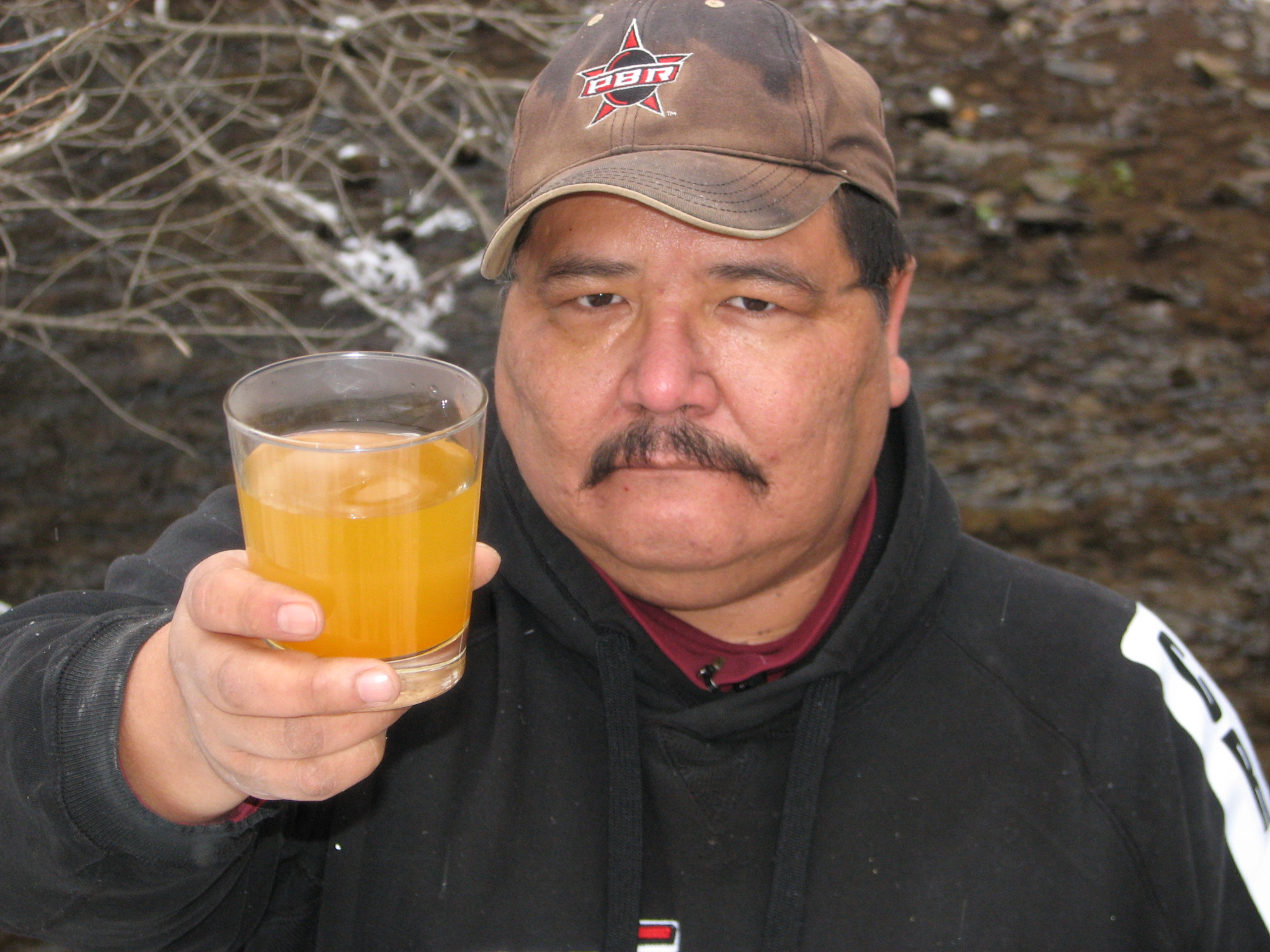 Dean Stiffarm of Fort Belknap, Mont., holds a glass of water contaminated by Pegasus Gold's Zortman-Landusky mine.