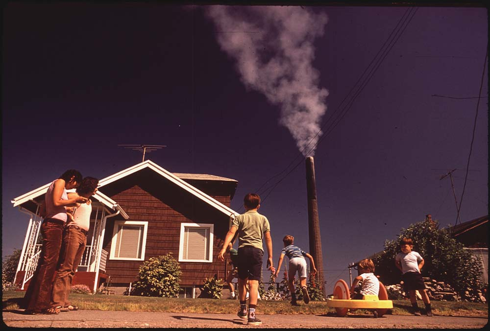 August, 1972: Children play in a yard while a Tacoma smelter stack showers the area with arsenic and lead residue in Ruston, Washington.