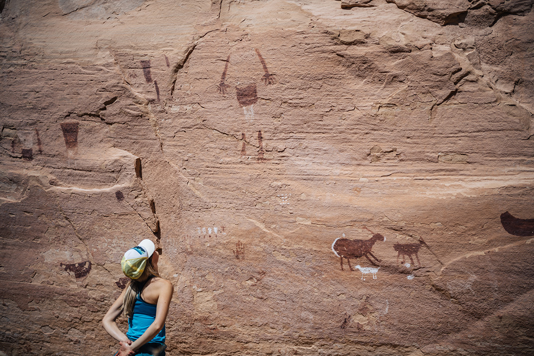A visitor looks at pictographs in Bears Ears' Grand Gulch