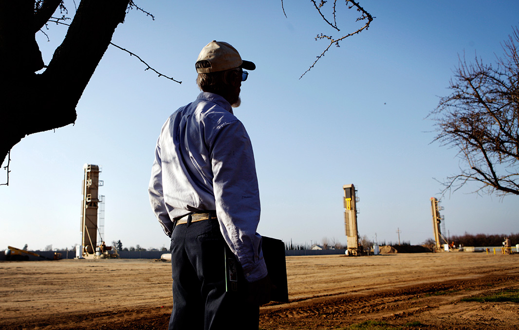 A farmer watches oil wells that have sprouted near almond orchards in Shafter, California.