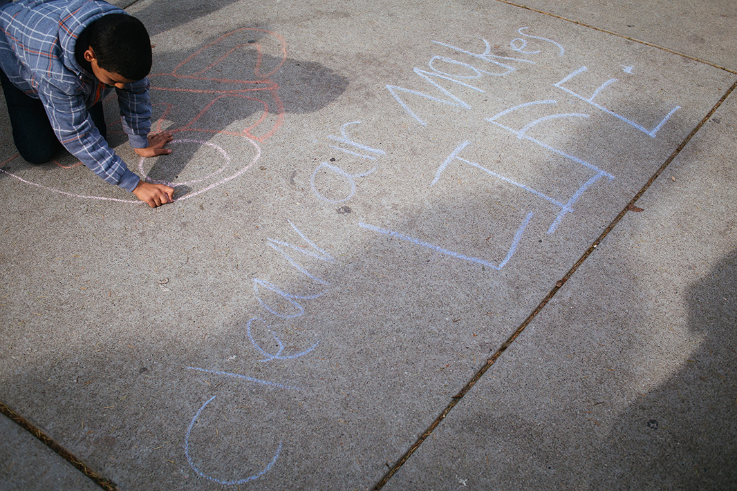 Saleh Sharay draws anti-smog and pro-health chalk art outside the hearing.