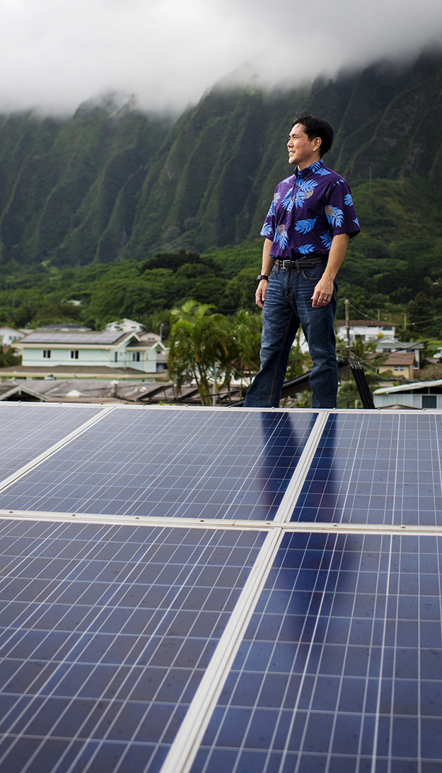 Earthjustice staff attorney Isaac Moriwake stands on his Oahu rooftop, which has been retrofitted with solar panels.