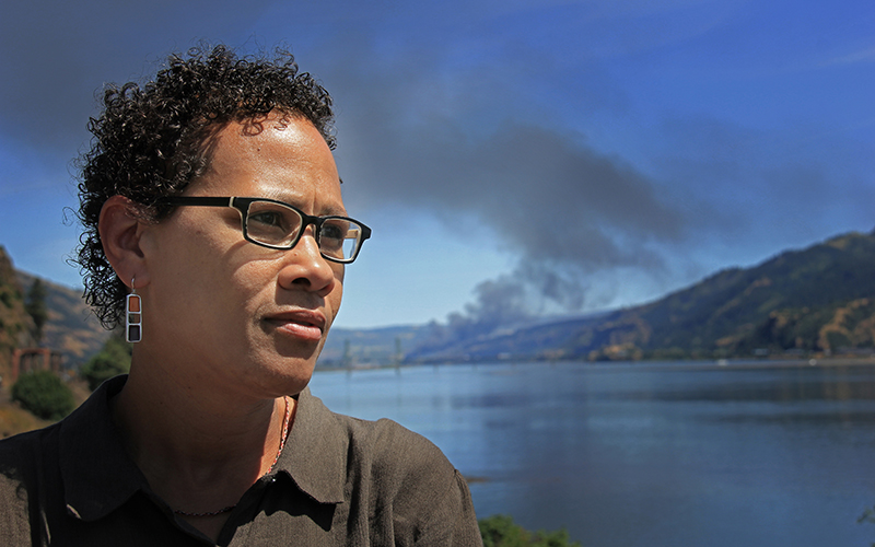 Earthjustice Senior Fossil Fuel Attorney, Adrienne Bloch, stands before the plumes of black smoke from the oil train derailment in Mosier.
