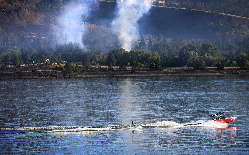A motorboat pulls a water skier past the smoldering site of the Mosier oil train accident.