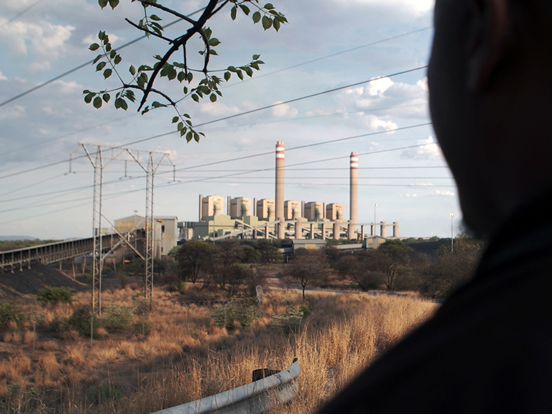 Silhouette of an activist looking at coal power plant in Lephalale.