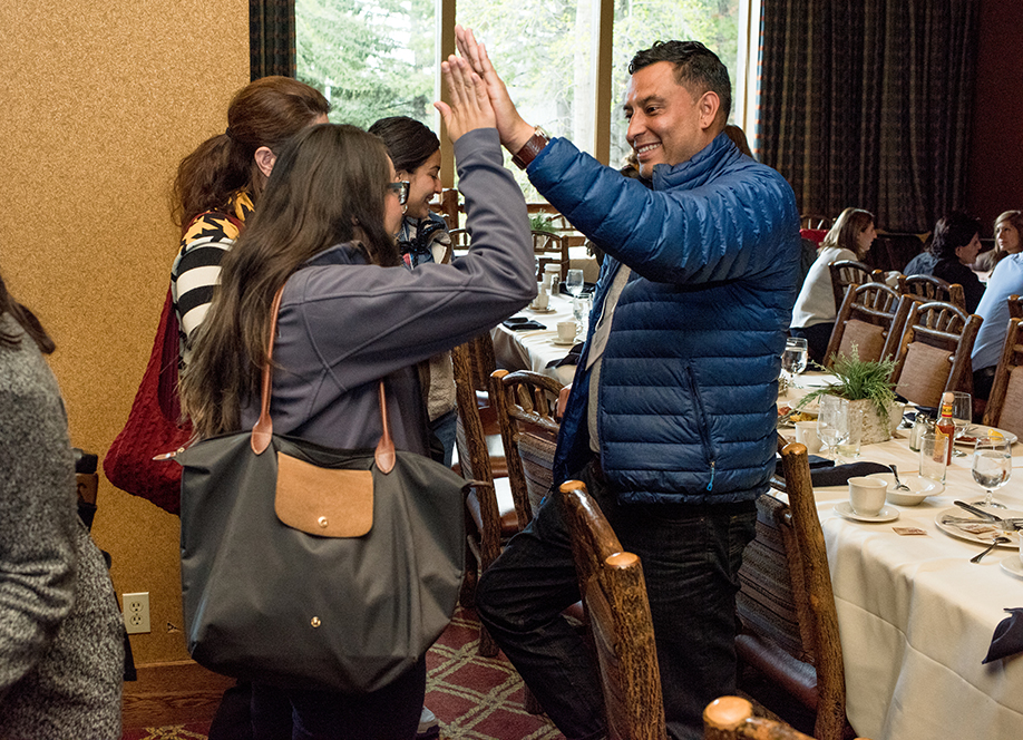 Earthjustice Senior Web Manager Raul Audelo high fives conference attendee Laura Fernandez.