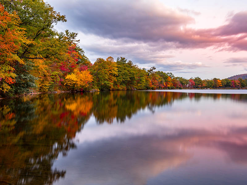 Fall foliage reflects in Hessian Lake at sunset, near Bear Mountain, NY.