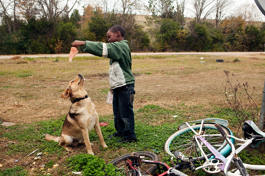 Timothy Moore, Jr., 8, plays with his dog.