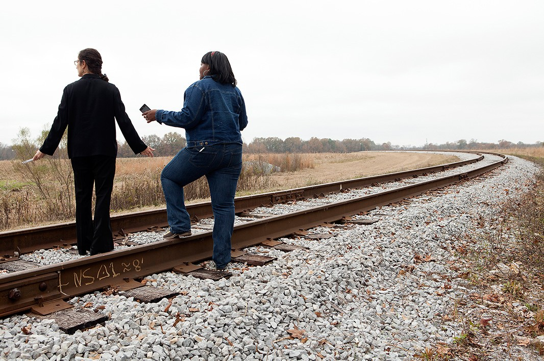 Standing on the train tracks that brought the coal ash, Esther Calhoun shows then-Earthjustice attorney Marianne Engelman Lado another view of land owned by Arrowhead Landfill.