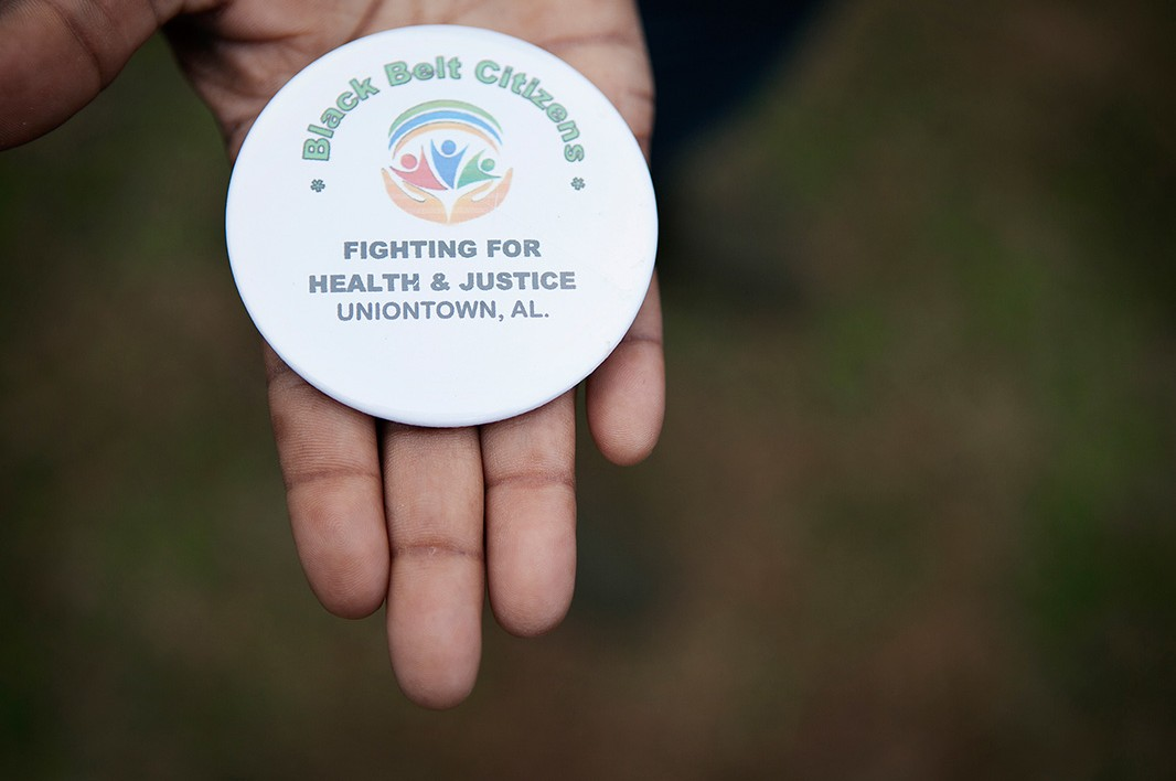 Esther holds a button from the Black Belt Citizens Fighting for Health & Justice.