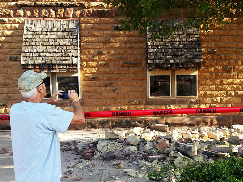 A man takes photos of damage to a building in downtown Pawnee, Okla., following a 5.6 magnitude earthquake in 2016. Geologists have linked fracking to an uptick in earthquakes.