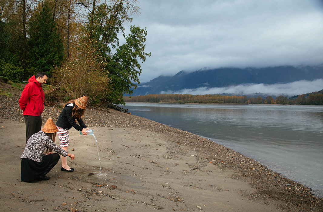 Suquamish Tribal Chairman Leonard Forsman and Kassia Smith and Shaylene Jefferson of the Suquamish Tribe pour water on the banks of the Fraser River during a ceremony in 2014 signifying the unity of the water.