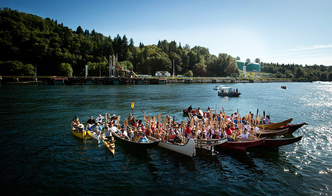 Members of the Suquamish and Tsleil-Waututh First Nations gather on the waters of Burrard Inlet at the Kinder Morgan Burnaby Terminal for a ceremony to show opposition to the $5 billion expansion of the TransMountain Pipeline, on September 1, 2012.