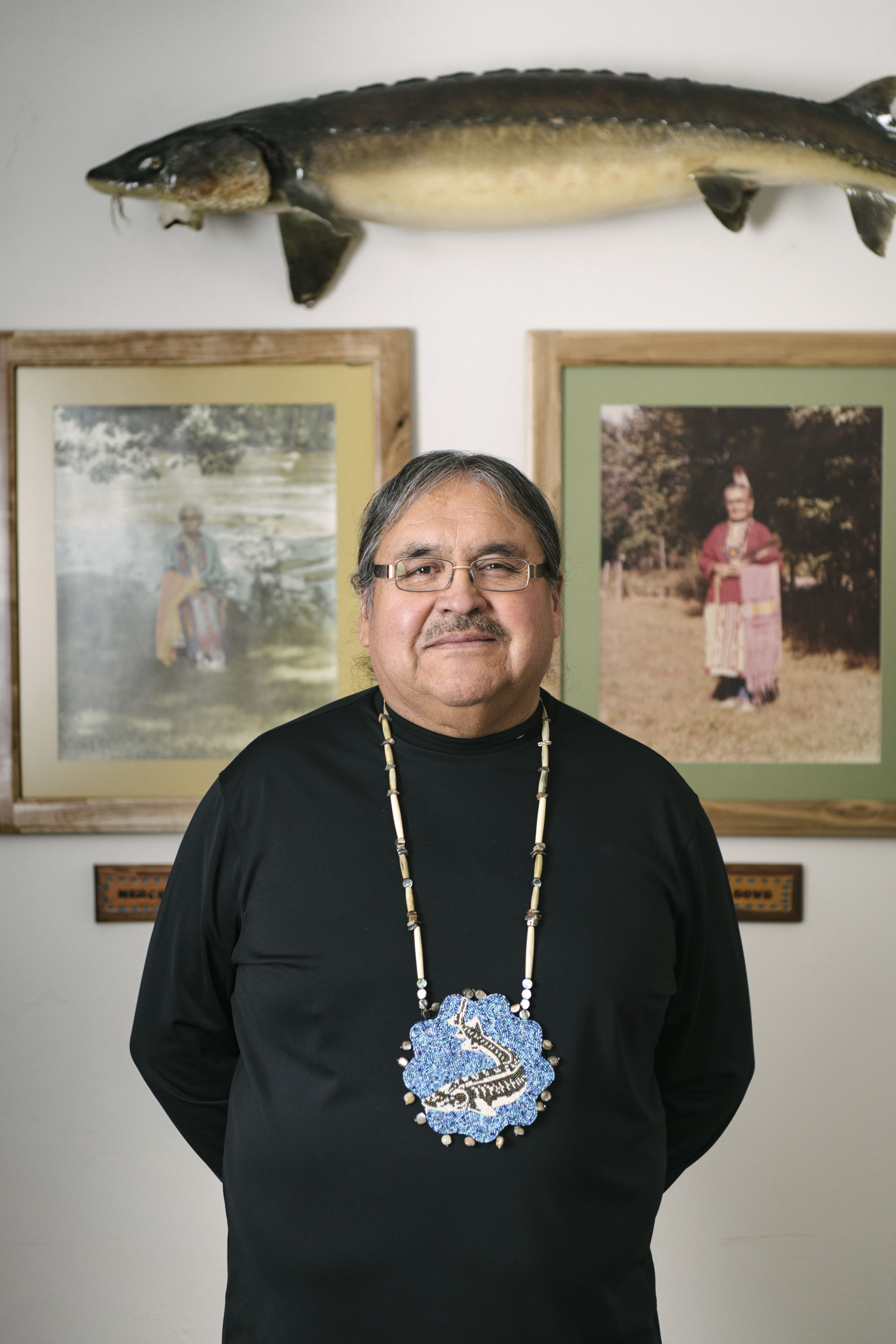 Historic Preservation Officer David Grignon at the Menominee Museum. Sturgeon is depicted in his traditional beadwork.