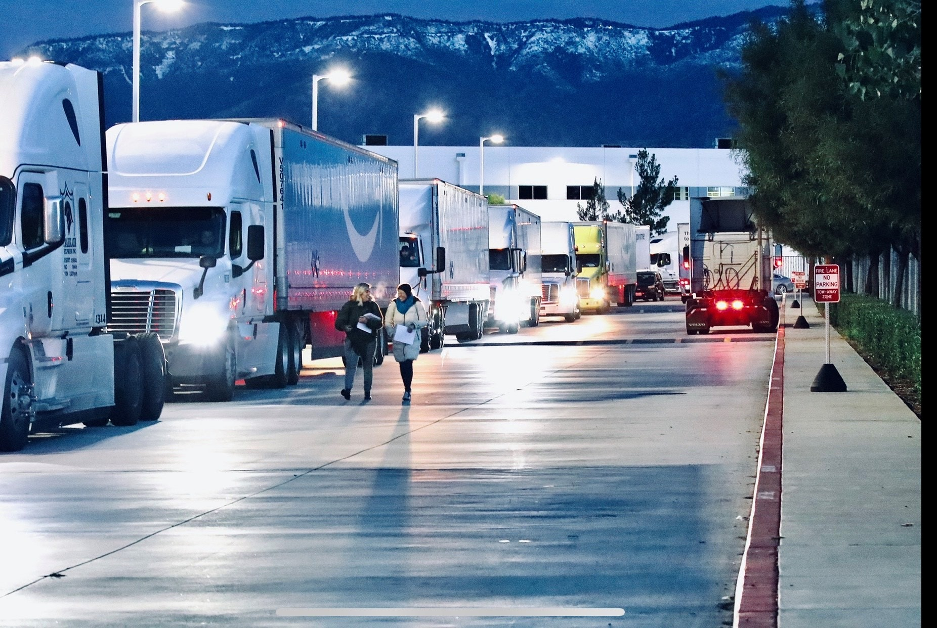 Freight trucks line up outside the Amazon ONT 2 and 5 facilities in San Bernardino. On the side of one truck is the AmazonSmile's logo. The street lights beside the trucks are shining. In the background is a mountainscape with snow. Two pedestrians in heavy coats are walking beside one another adjacent to the trucks.