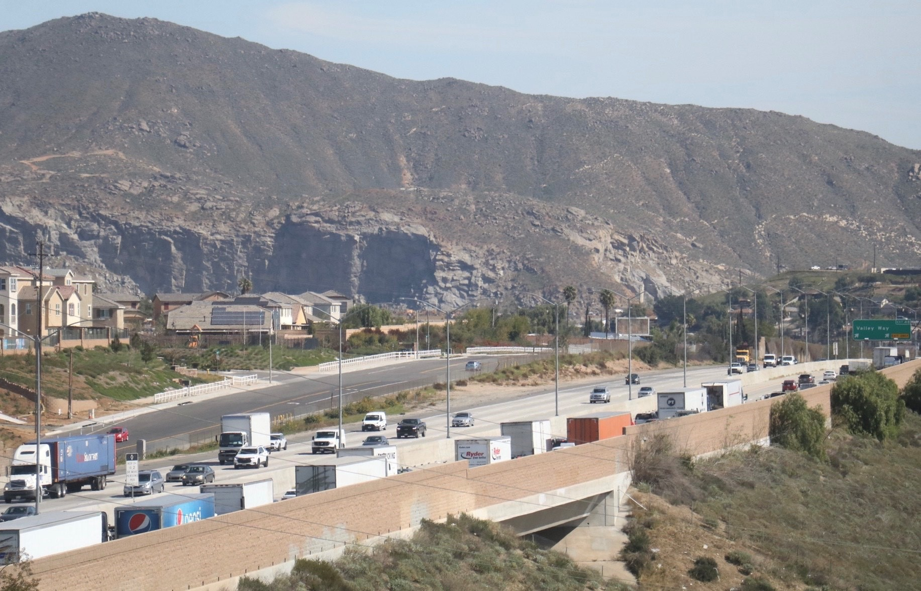 Image of the 60 freeway that runs through Jurupa Valley, California, near the offices of the Center for Community Action and Environmental Justice. In the background is a mountainscape. Beside the freeway are some multi-floor buildings. There are numerous trucks and a few cars on both directions of the freeway.