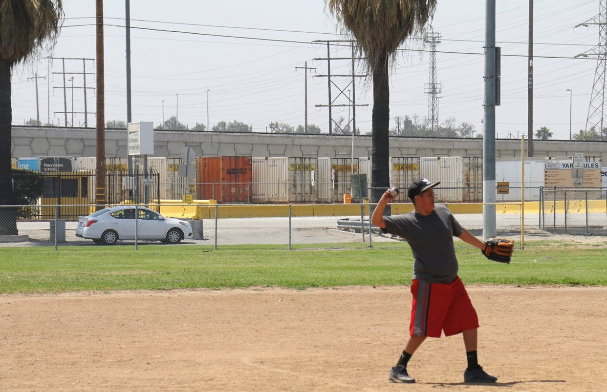 A person wearing a black cap, grey short sleeve tee, red shorts, black socks and shoes, and a baseball glove throws a baseball in San Bernardino's Nunez Park, across the street from the BNSF Railroad. In the background are two tall palm trees, numerous freight containers, and multiple powerlines