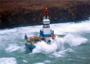 Waves crash over the conical drilling unit Kulluk where it sits aground on the southeast side of Sitkalidak Island, AK, Jan. 1, 2013. (U.S. Coast Guard photo by Petty Officer 3rd Class Jonathan Klingenberg.)