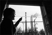 Marti Blake points at the coal-fired power plant that dominates the view from her living room, just outside of Pittsburgh, Pennsylvania. (Chris Jordan-Bloch / Earthjustice)