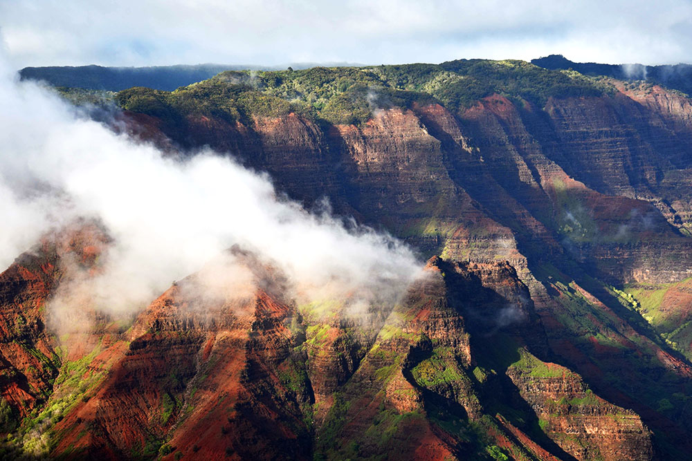 Afternoon fog rolls in over the Waimea canyon in Kaua'i, Hawai'i.