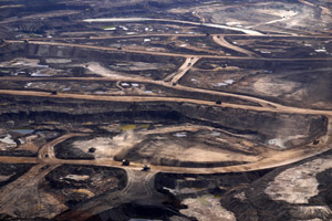 Tar sands mining operations destroy forests and wetlands, with vast drilling infrastructure, open pit mines, and toxic wastewater ponds up to three miles wide, permanently damaging the environment. (Velcrow Ripper / Flickr)
