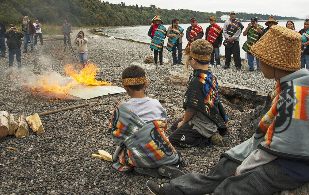 Young participants observing the flames at the symbolic check burning ceremony.