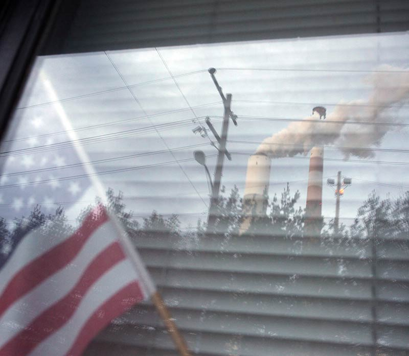 The Cheswick coal-fired power plant in Pennsylvania, reflected in a window of a home in Springdale.
