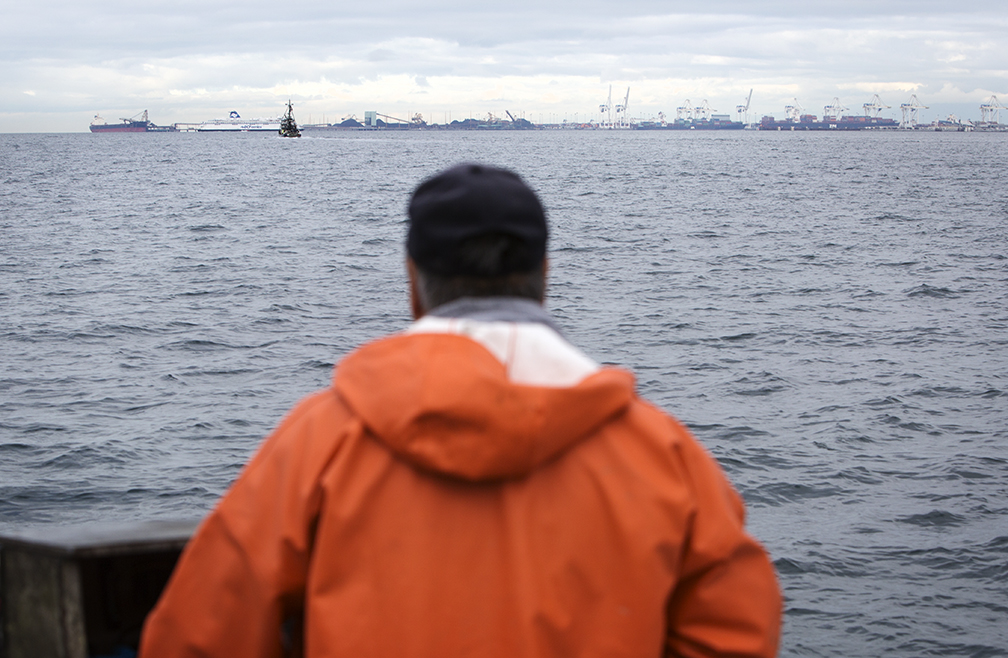 A Lummi fisherman stares across the water at the Westshore coal terminal in British Columbia, similar to the proposed Gateway Pacific Terminal.