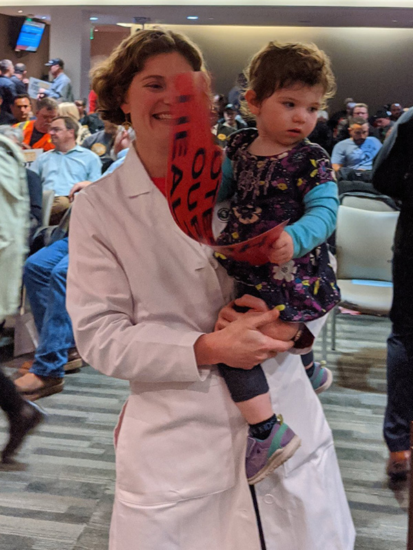 Local pediatrician Dr. Amanda Millstein attends a public meeting with her daughter in Richmond to urge the city to take action on coal dust from the Levin Terminal.