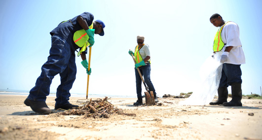 Contractors clean up tar balls along Crystal Beach on the Bolivar Peninsula. July 10, 2010. (U.S. Coast Guard Photo / PO2 Prentice Danner)