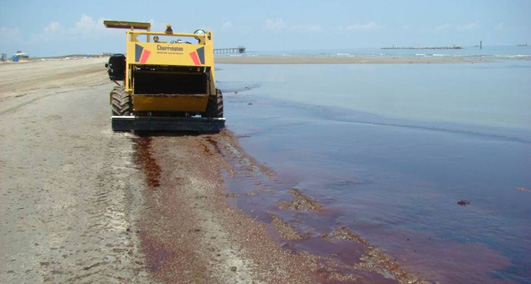 Crews aboard beach clean-up vehicles sift oil on the southeast Louisiana shoreline. June 10, 2010. (U.S. Coast Guard Photo / PO1 Luke Pinneo)