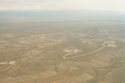 Aerial photo of active drilling operations in Wyoming's Pinedale Anticline natural gas field in August 2002.  (SkyTruth)