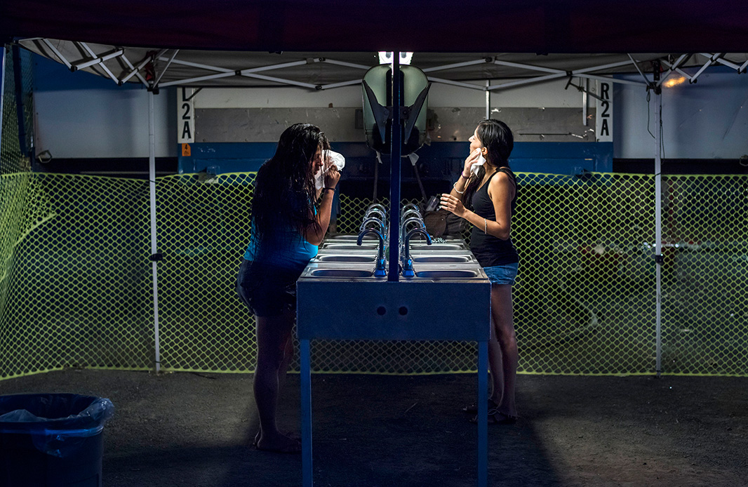 Sisters Amanda Perez, left, and Miranda Perez dry their faces after taking showers at the portable showers available to use for free at the Iglesia Emmanuel Church in Porterville, California on April 13, 2015.