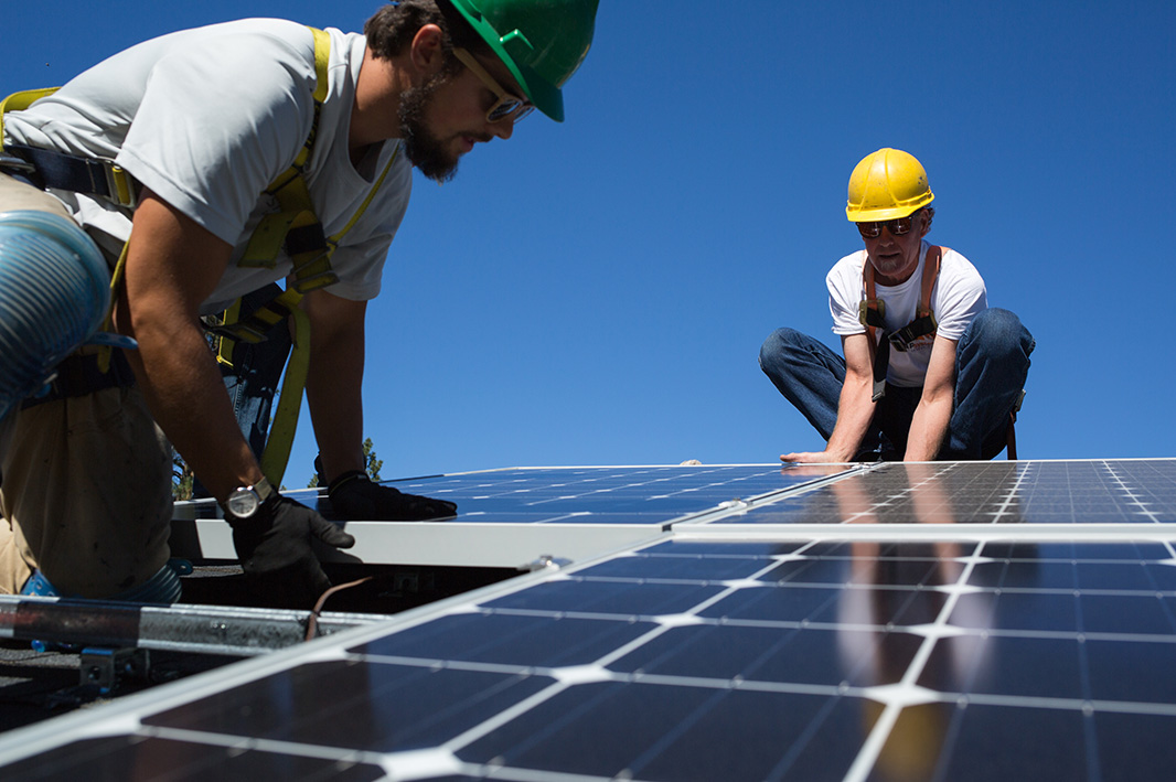 Technicians install rooftop solar panels in Spokane, Washington.