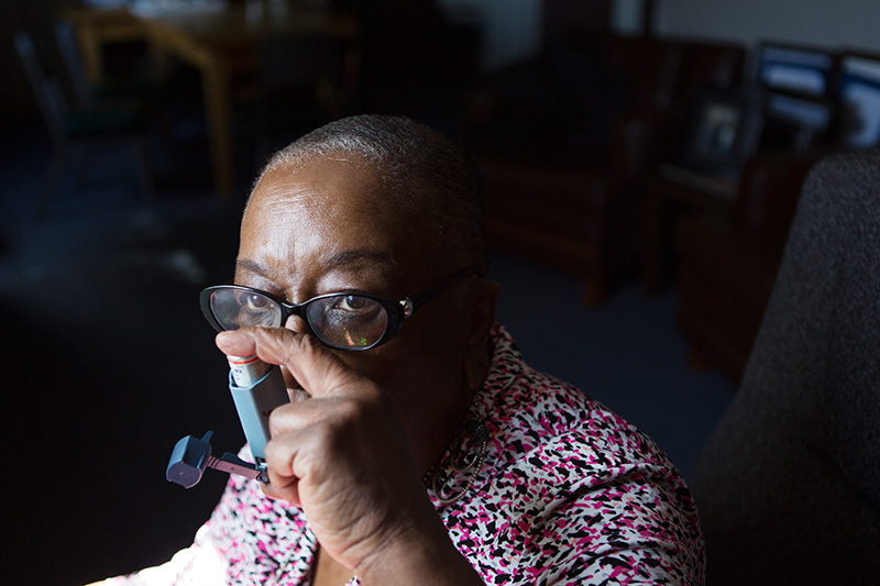 Gordon takes a breath of her asthma medication.  West Oakland residents are twice as likely to go to the emergency room with asthma as other people in their county.
