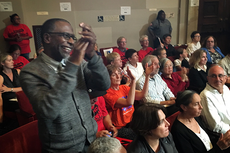 Rev. Ken Chambers of West Side Missionary Baptist Church applauds following the City Council vote on June 27, 2016.