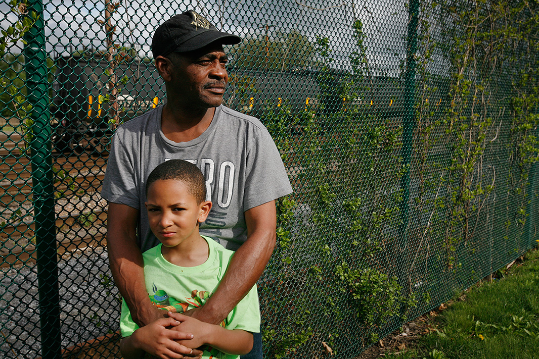 Be Be White and his son Brayton stand along the fence that separates the railroad tracks from the apartments.