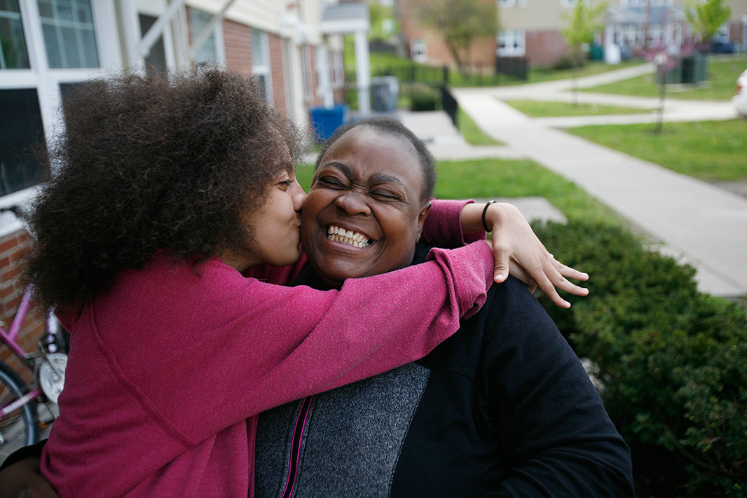 Leatha, 13 years old, gives her mom, Angela Scott, a kiss outside their home at the Ezra Prentice Homes.  They have lived in the complex for six years.