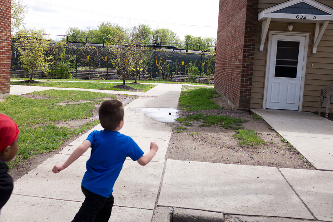 Antonio, 5 years old, runs through the complex with a friend.  Antonio's mother said that late at night when the train cars are uncoupling or coupling they create a loud noise and the whole apartment can shake, scaring Antonio and his older sister who come running to get into their mom's bed.