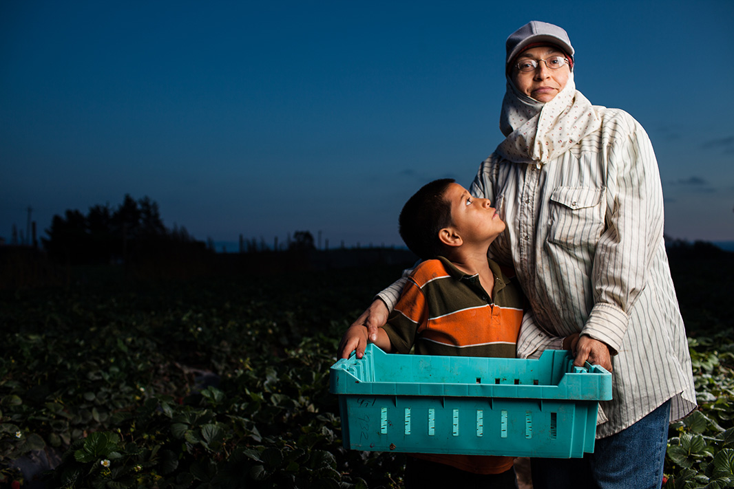 Maria Aguilera, a farmworker, and her son stand in a strawberry field in California.