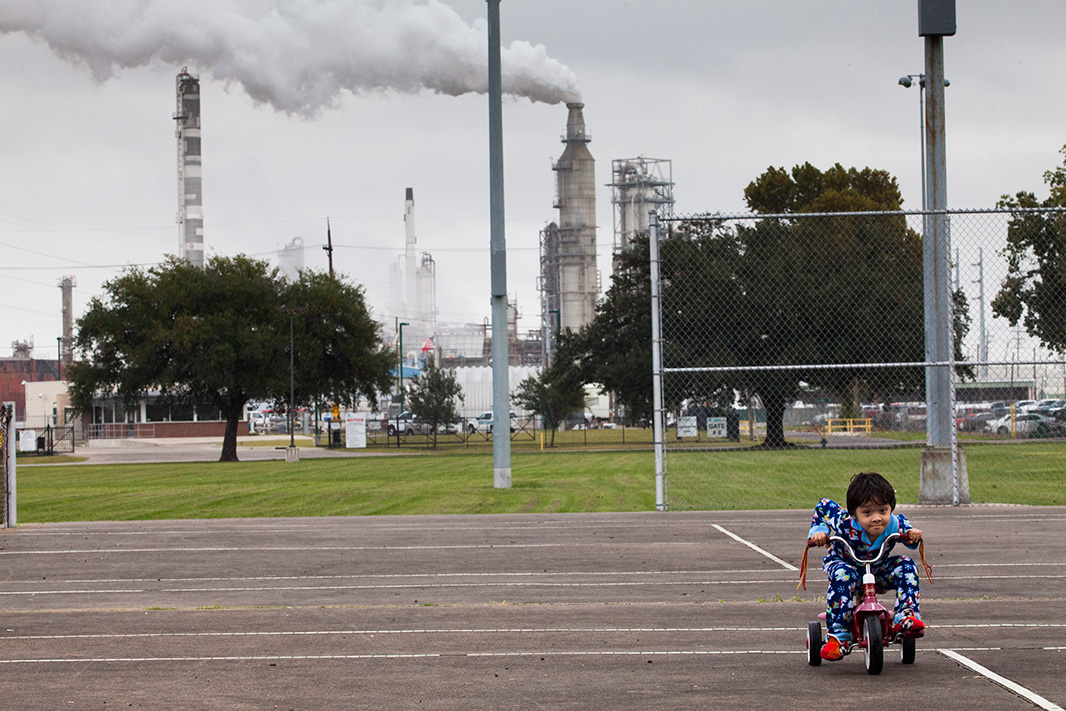 Chrisangel plays in the shadows of a refinery in the Manchester neighborhood of Houston, Texas.