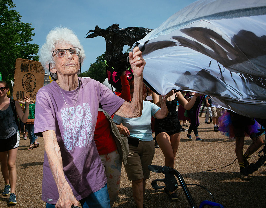 Eve Tetaz marches in the Peoples Climate March. The 84-year-old was marching while holding a banner with one hand and her walker with the other.