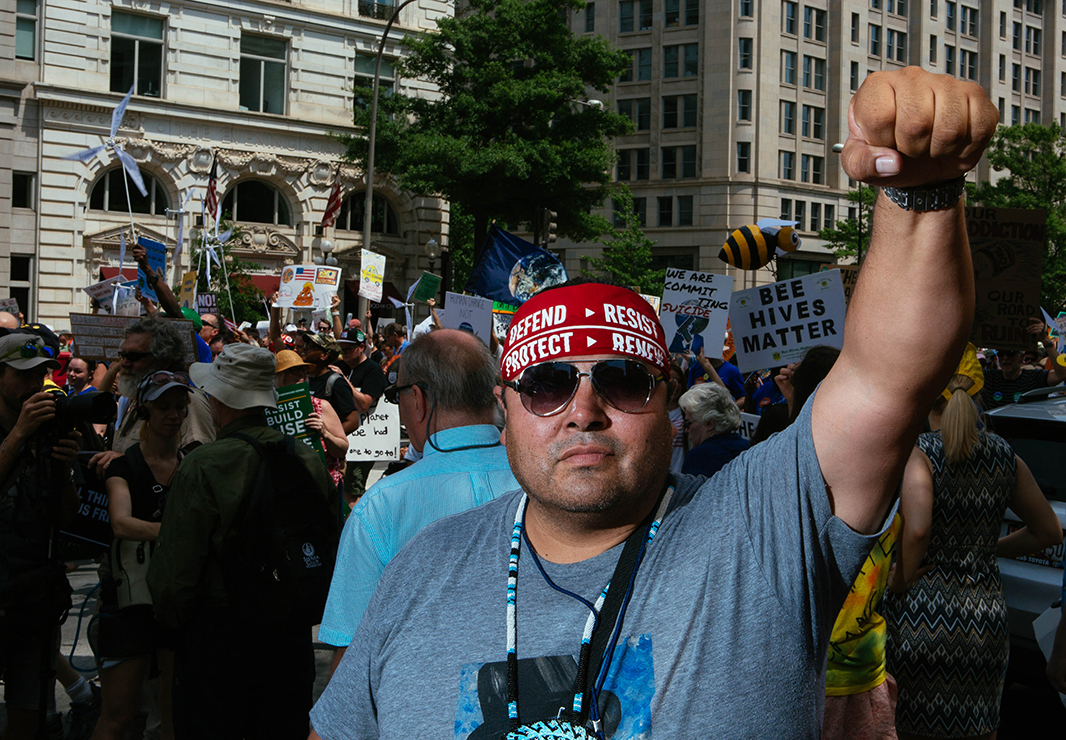 Myron Dewey raises his fist as the Peoples Climate March moves past the new Trump Hotel in Washington, D.C. Dewey was a drone operator at Standing Rock whose footage kept the Water Protectors aware of pipeline operations and kept the world informed about the story of the resistance.