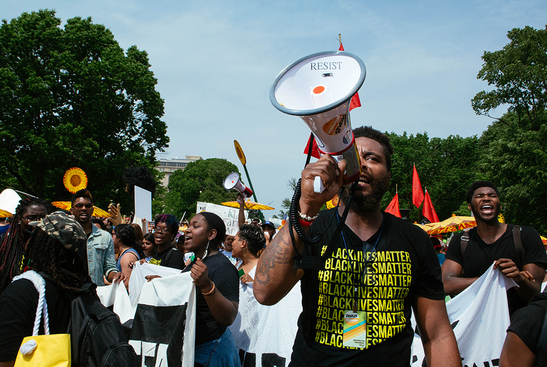 Shawn Williams, a community organizer, rallies people as the march passes in front of the White House. Williams marched with a large coalition from Black Lives Matter.