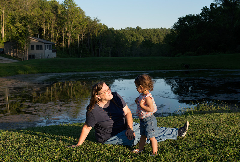 Schumacher, with her granddaughter. The pond behind them filled with debris from a pipeline project during a rainstorm.