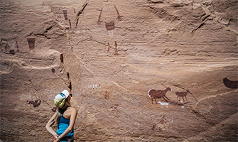 A visitor looks at pictographs at Bears Ears National Monument.